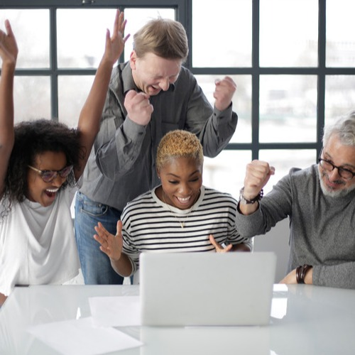 Canva - Excited multiracial colleagues enjoying triumph together in front of laptop in office